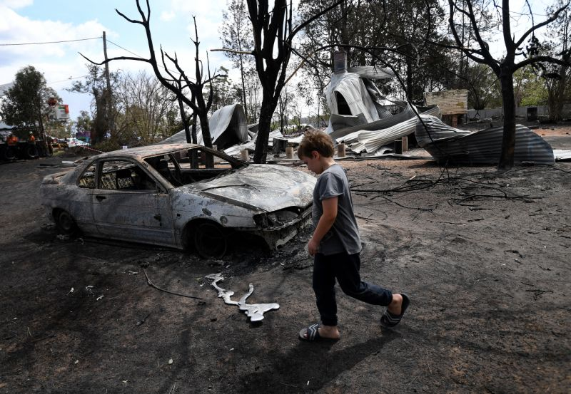 Eight year-old Jarrod McInnes walks next to the remains of a house that his family was about to buy and was destroyed by bushfires in Rappville. Source: AAP Image/Dan Peled.